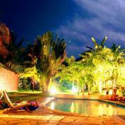 une vue de nuit de la piscine et du jardin