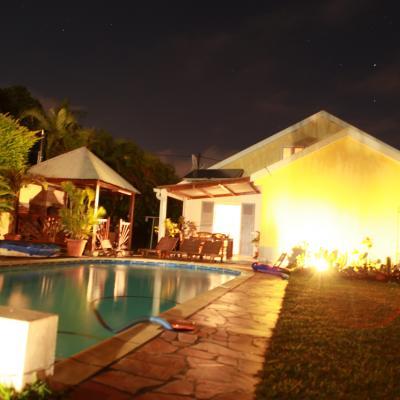 la piscine et la façade de la villa de nuit